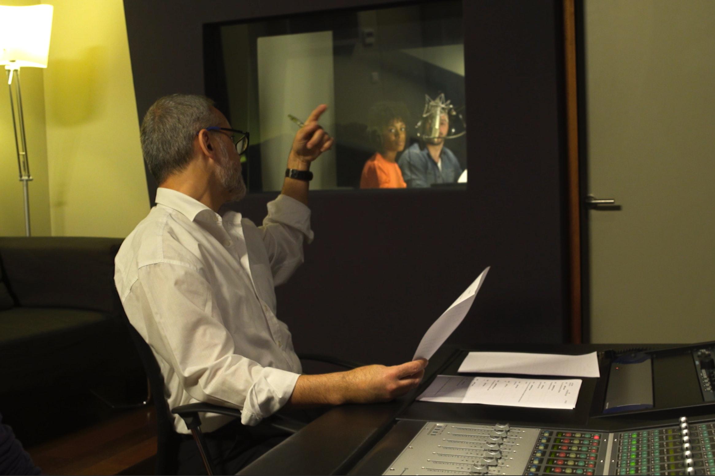 Directeur artistique donnant des consignes de doublage à des comédiens dans studio d'enregistrement