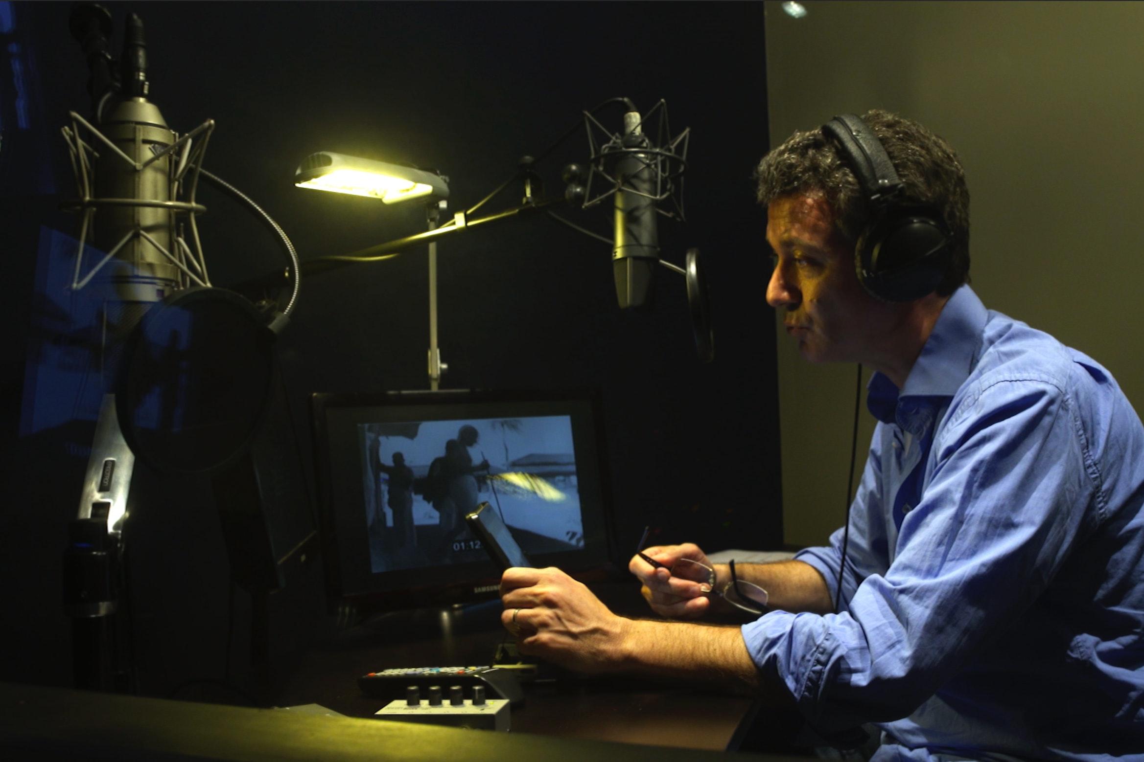 Comédien pendant séance de doublage d'enregistrement de voix off dans cabine avec microphone