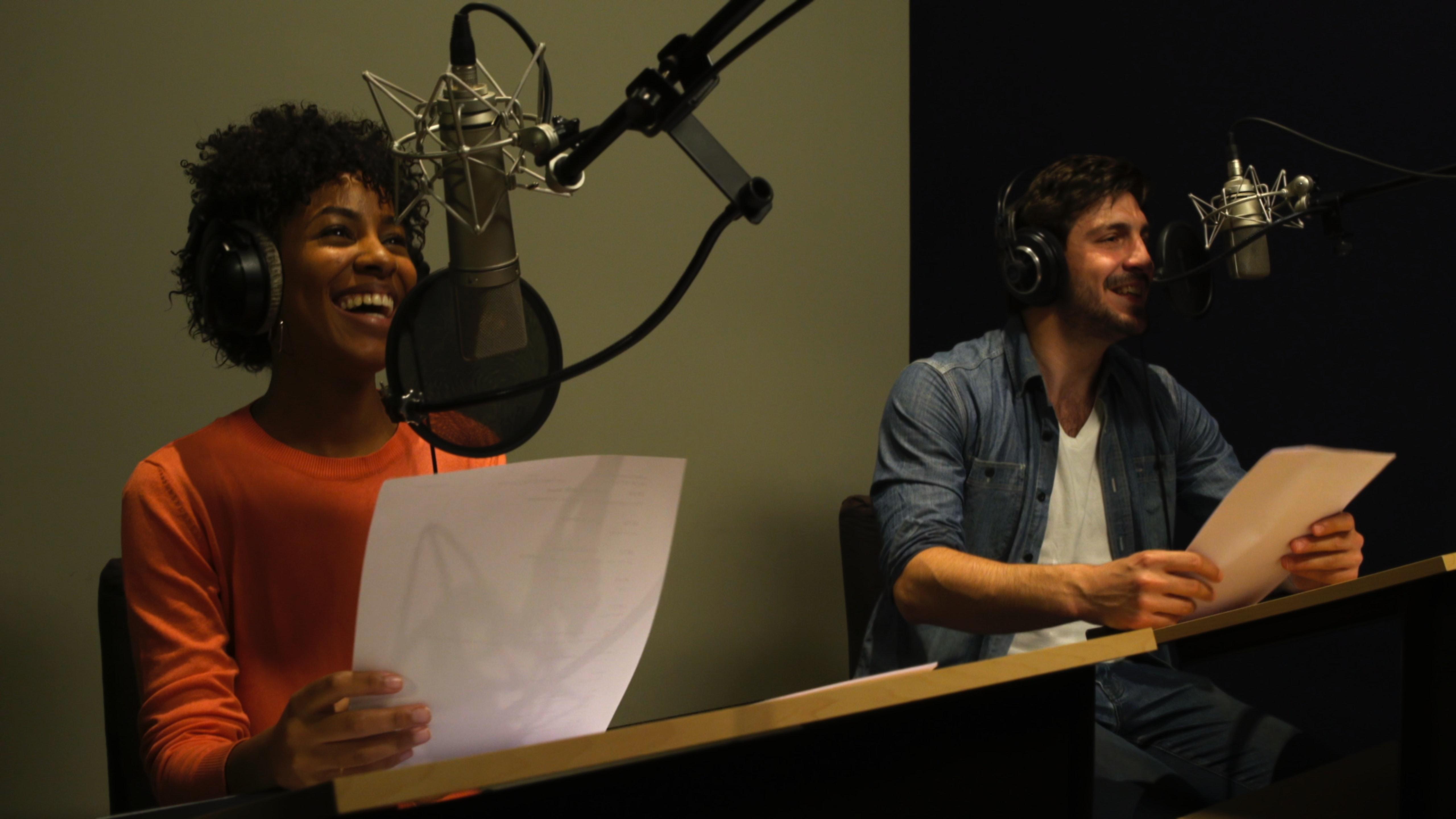 Un acteur et une actrice souriants en séance d'enregistrement de voix de doublage.